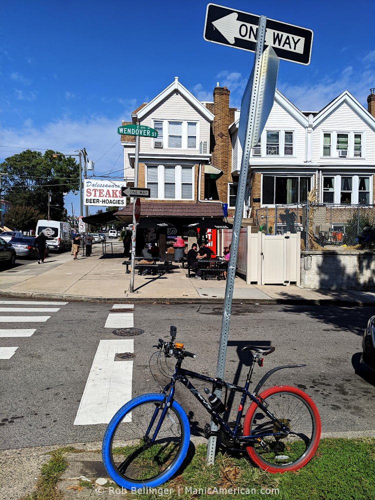 a bike with red and blue tires locked to a one way sign across from a beer and hoagie restaurant