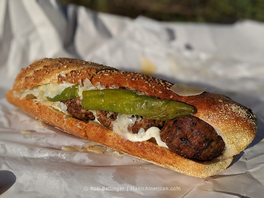 a meatball hoagie topped with a green long hot pepper
