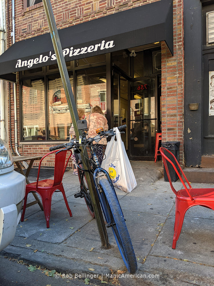 a bike with a bag hanging from its handlebars parked in front of a restaurant called Angelo's Pizzeria
