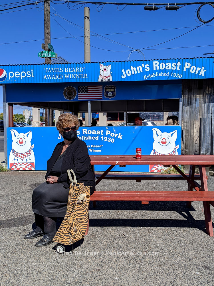 an older woman wearing all black and a face mask sits with her leopard print luggage at the bench of a hoagie restaurant