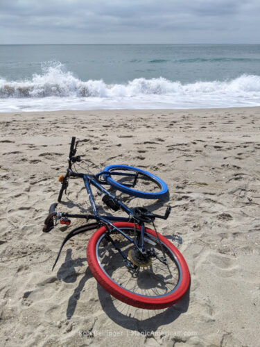 A bike with one red and one blue tire lying on rockaway beach as a wave breaks in the background