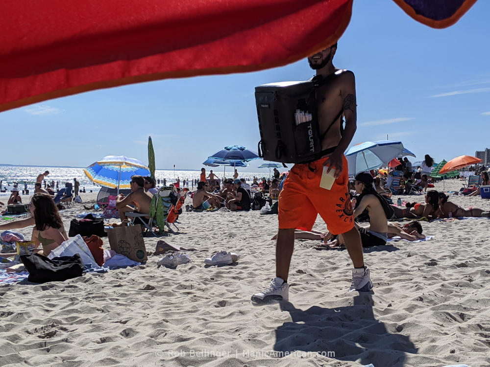 a shirtless man selling alcoholic beverages on rockaway beach using a cooler backpack mounted to his chest. his face is obscured by a beach umbrella