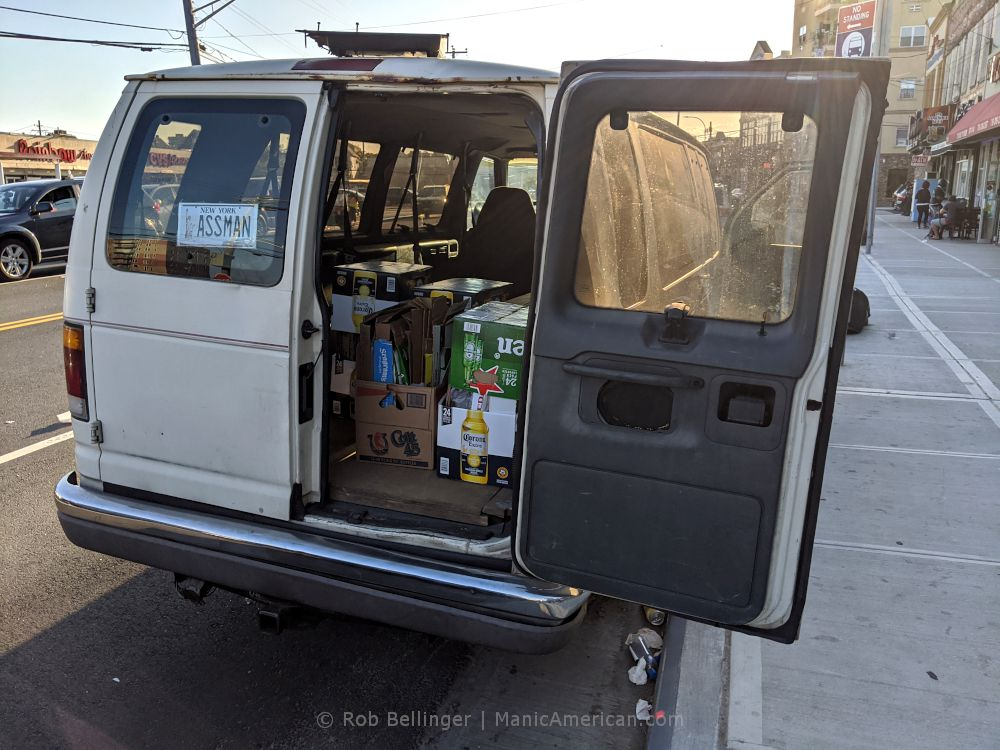 a white van with rear door open revealving cases of beer, with a fake license plate that reads ASSMAN