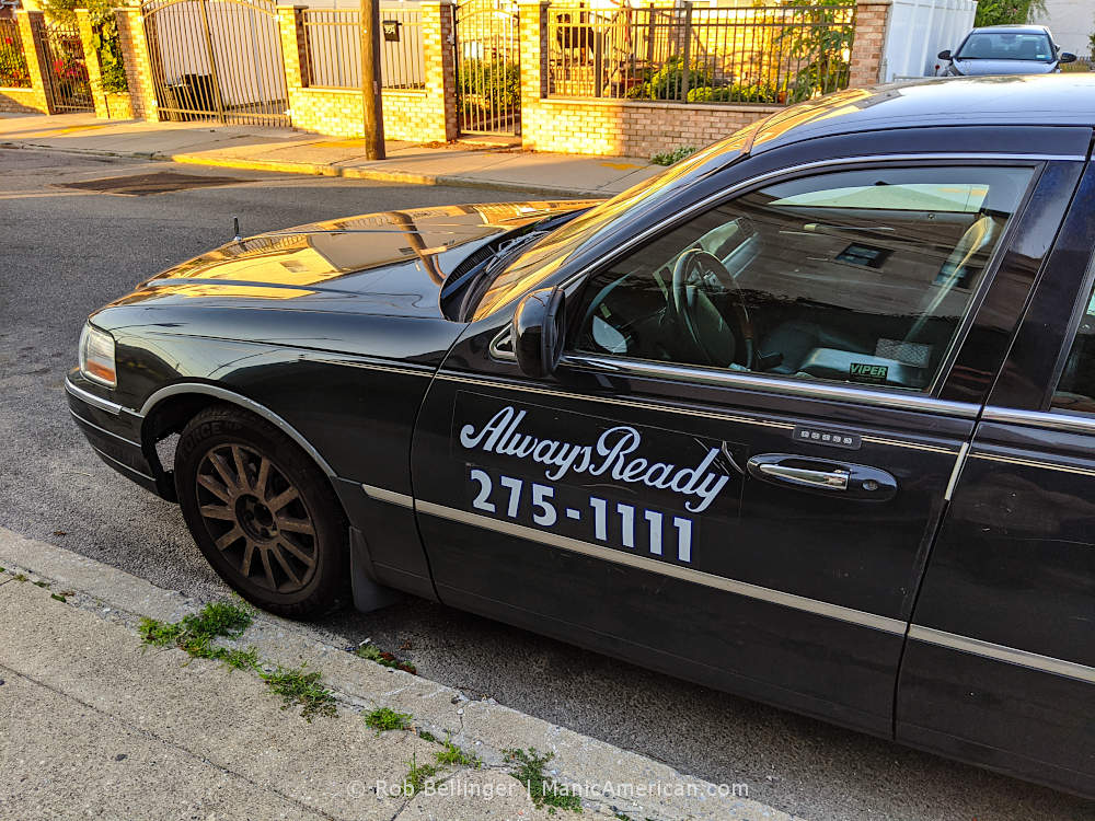 """an old lincoln town car with decal displaying the words """"always ready"""" at sunset"""