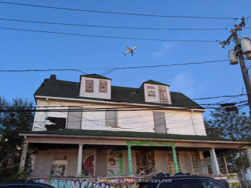 a plane takes off over an abandoned house covered in graffiti in rockaway beach