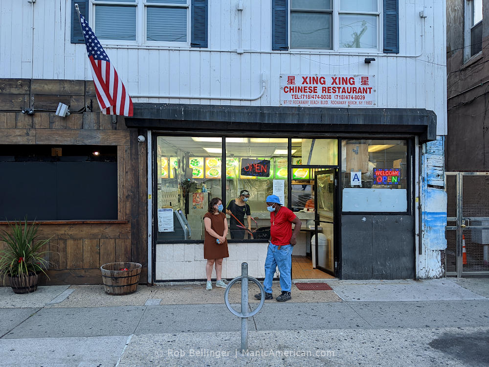 A man leaves a small Chinese-American restaurant on Rockaway Beach while a woman waits for her order and a worker mops the floor