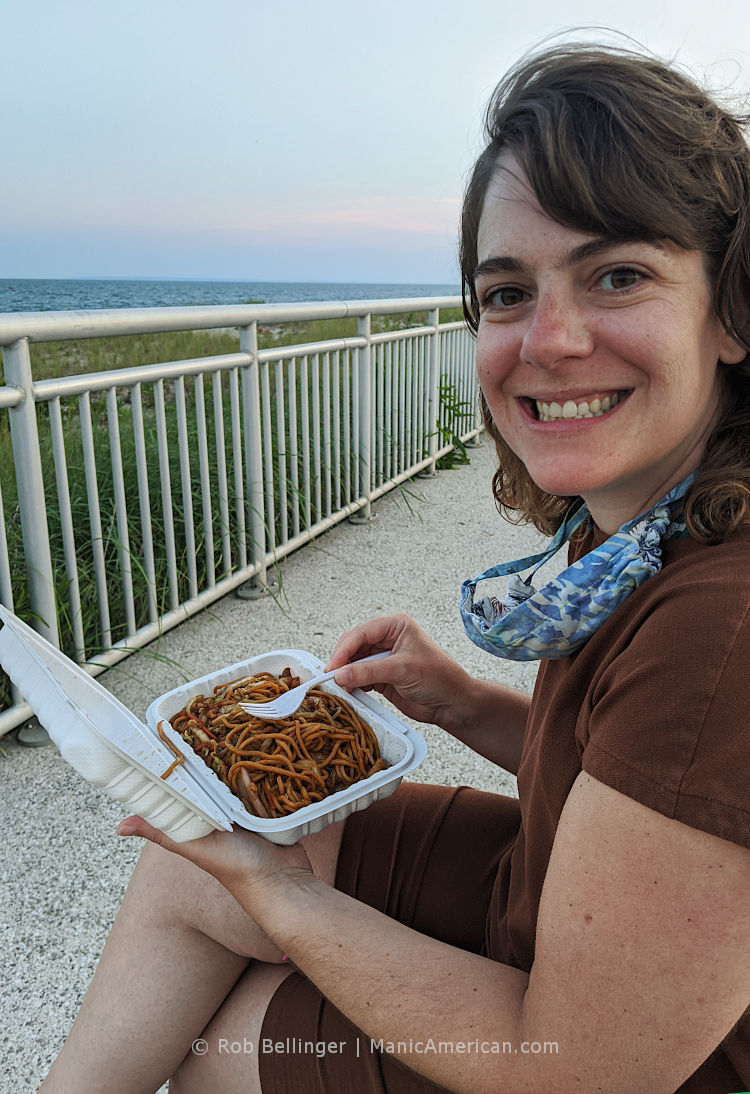 a young woman eats a plate of lo mein noodles on the rockaway beach boardwalk