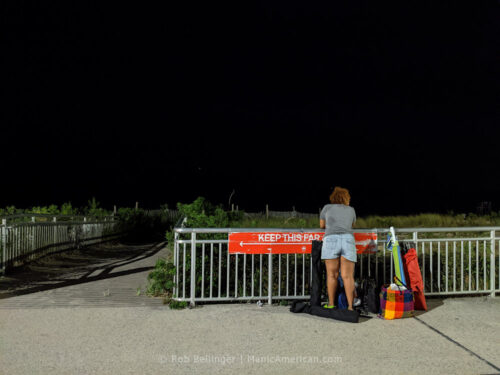 a woman looks at the ocean from the rockaway beach boardwalk, with the now-famous NYC Parks social distancing sign showing how far 6 feet is just in front of her