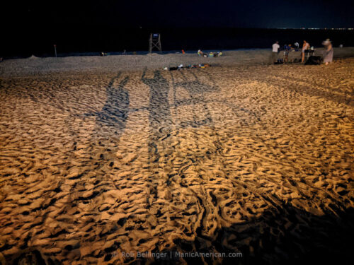 on the rockaway beach sand, two long, shadowed figures wave at the camera