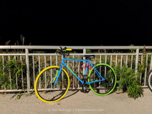 a brightly colored bike chained to the rockaway beach boardwalk at night. the bike is a Kent Ridgeland, a $99 fixed-gear bike from Walmart, which sold out at the very beginning of the pandemic bike boom.