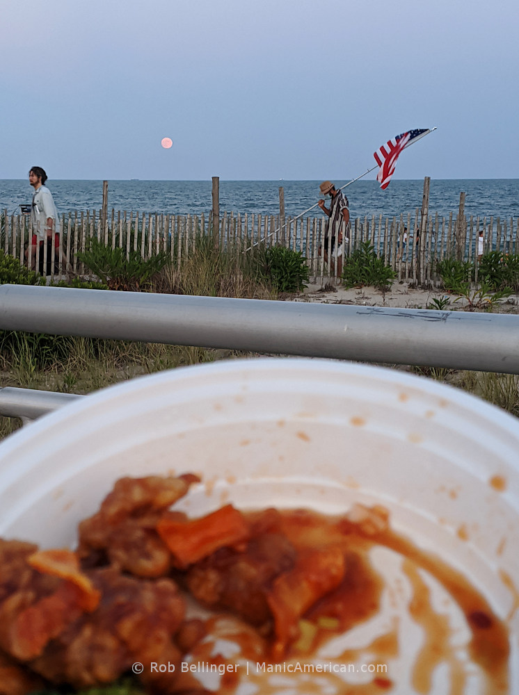 a full moon rises over the ocean, while a man carries an american flag on the rockaway beach boardwalk, viewed from behind a takeout container of orange beef