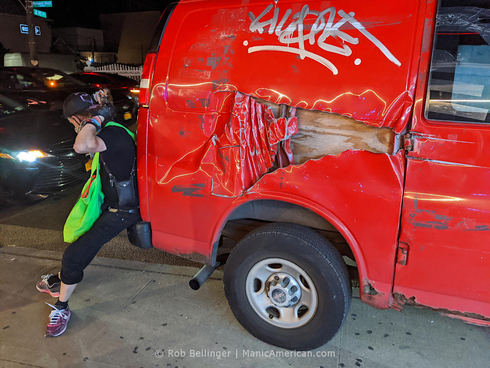 a young man leans against a graffitied red van with extensive damage in rockaway beach