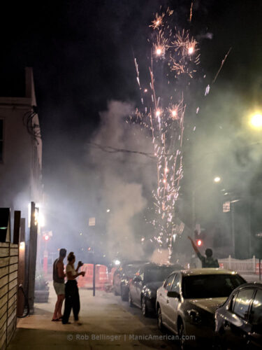 revelers celebrate in the streets of rockaway beach as fireworks explode