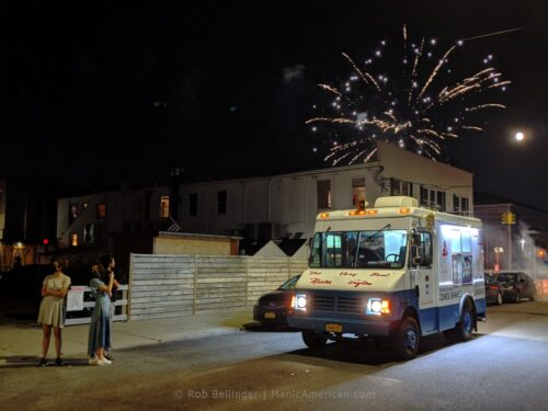 fireworks explode over an ice cream truck in rockaway beach as three tourists take photos