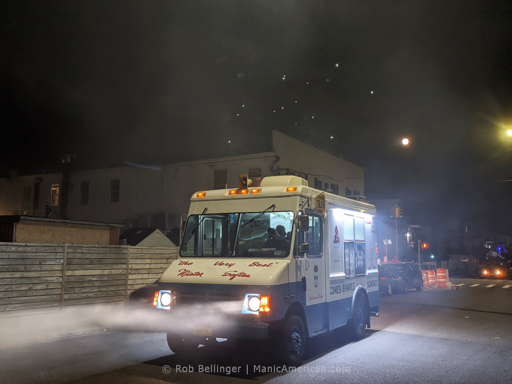 headlights from an ice cream truck shine through heavy white smoke from fireworks