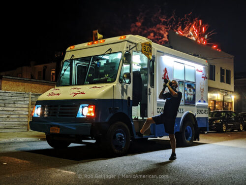 while fireworks explode in the background over rockaway beach, the driver of an ice cream truck steps out of the truck and uses a large camera pointed skyward