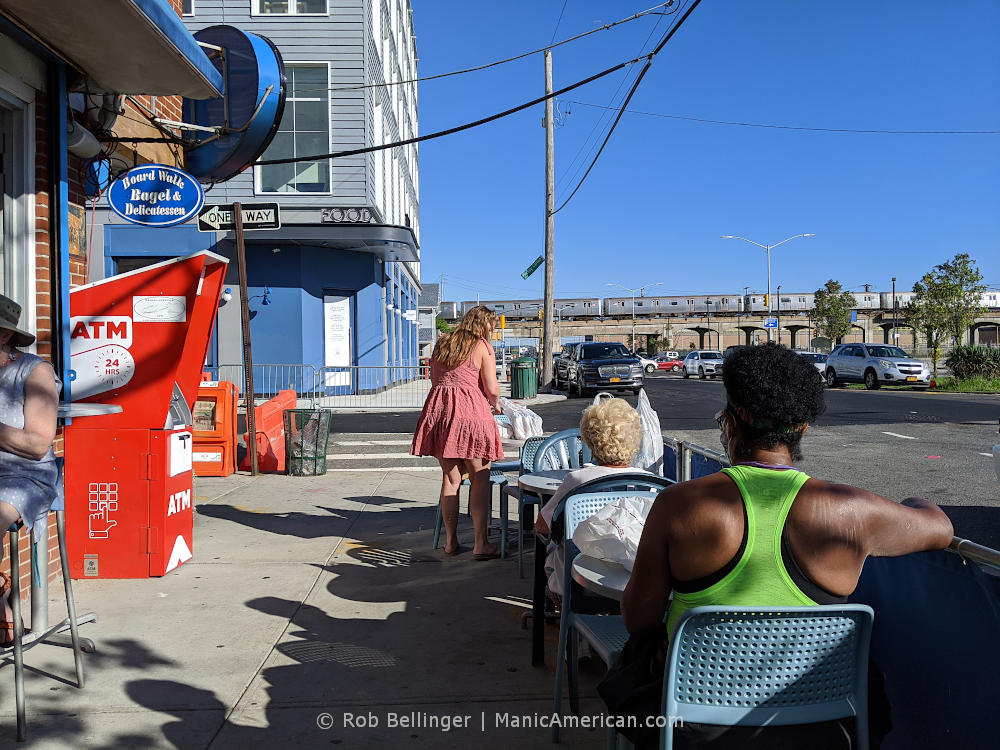 a sidewalk dining area at a deli restaurant with a rockaway beach subway train passing in the background