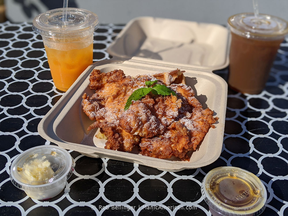 slices of fried chicken over waffles with cups of iced coffee and honey butter at bernadette's in rockaway beach