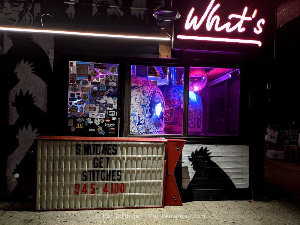 """two brick pizza ovens inside a restaurant with a neon sign that says """"whit's,"""" with a hand-lettered sign stating """"snithces get stitches,"""" at whit's end restaurant in rockaway beach"""