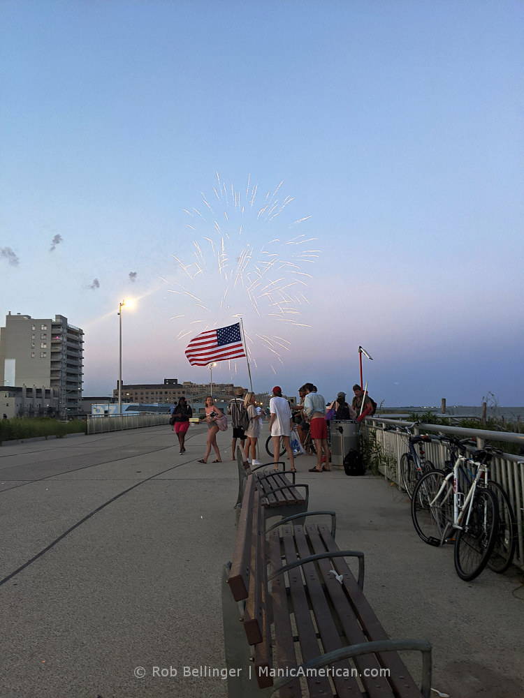 fireworks exploding over the rockaway beach boardwalk while a group of people display an american flag