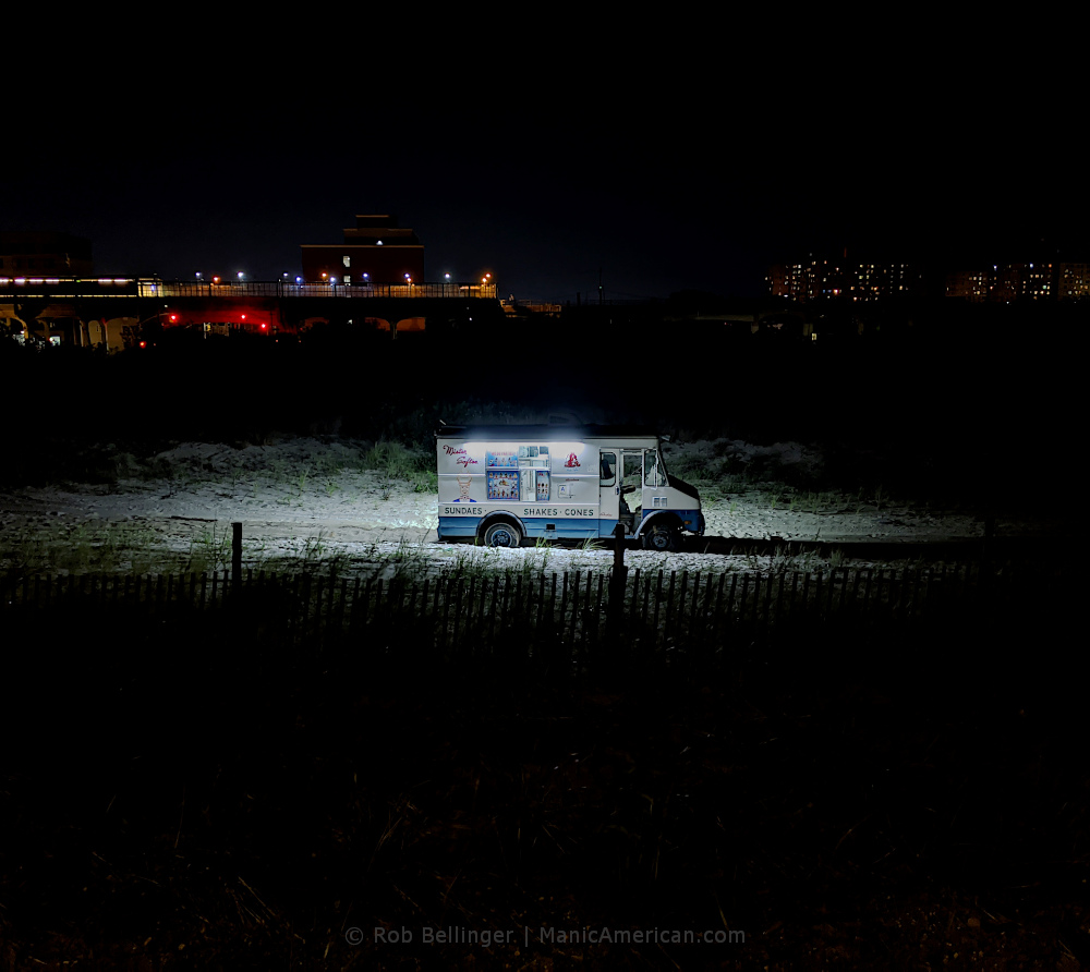 a lone ice cream truck on rockaway beach at night with subway station in background