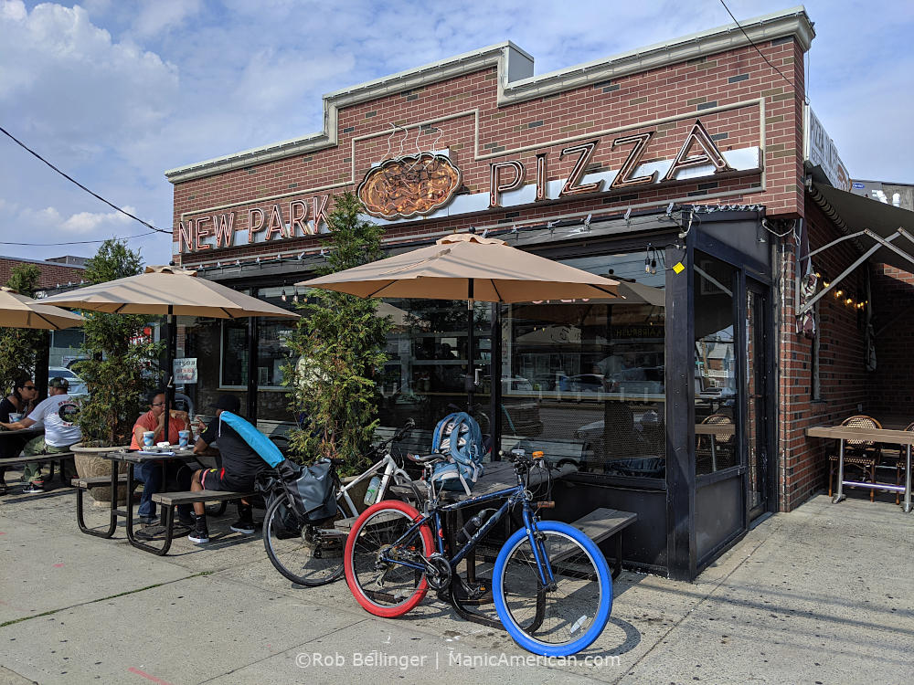 the exterior of new park pizza in howard beach queens showing picnic tables and two bikes